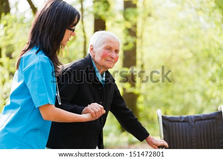 Caring nurse or doctor helping elderly patient to sit down on her wheelchair. - stock photo