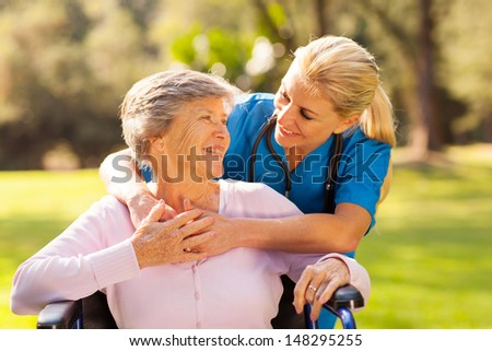 caring nurse with senior patient outdoors - stock photo