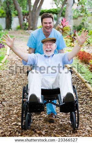 Caring nursing home orderly pops a wheelie with an elderly man's wheelchair.  They are having fun. - stock photo