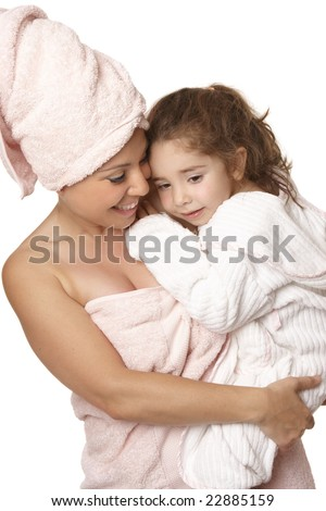 Caring nurturing mother cuddles her daughter at bathtime - stock photo