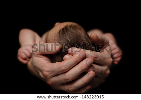 Caring parent's hands - father and newborn