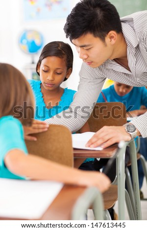 caring primary educator helping a student in classroom - stock photo