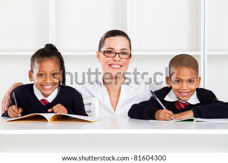 caring primary teacher and students in classroom - stock photo