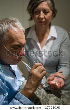 Caring senior wife holding drugs for her sick husband - stock photo