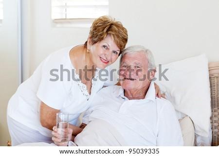 caring senior wife taking care of ill husband - stock photo