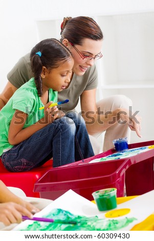 caring teacher help preschool girl painting picture - stock photo