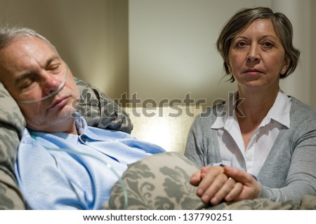 Caring wife holding sick senior husband's hands lying in bed - stock photo