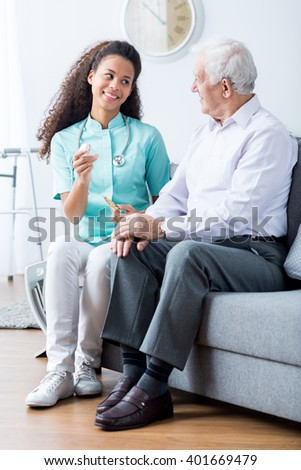 Caring young caregiver in uniform reminding older man to take medicine - stock photo