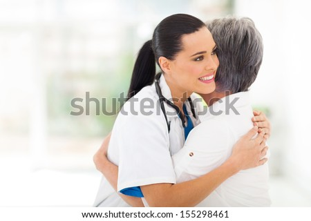caring young medical doctor hugging senior patient - stock photo