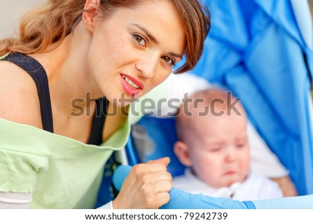 Caring young mother hugging sitting in stroller crying baby - stock photo