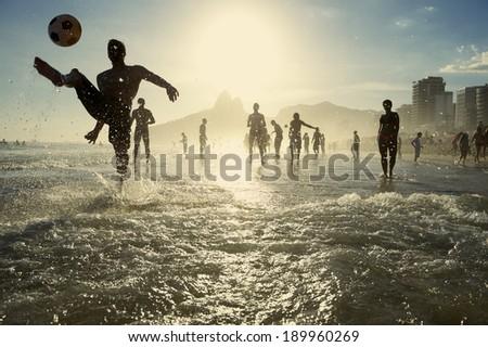 Carioca Brazilians playing altinho beach football in silhouettes kicking soccer balls in the waves of Ipanema Beach Rio de Janeiro Brazil - stock photo
