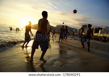 Carioca Brazilians playing altinho futebol beach football kicking soccer balls at sunset Ipanema Beach Rio de Janeiro  - stock photo
