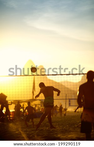 Carioca Brazilians Rio de Janeiro Brazil sunset beach futevolei volleyball game against a silhouette of Dois Irmaos Mountain on Ipanema Beach - stock photo