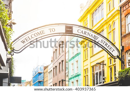 Carmaby street sign in London with some colorful houses on background and sun beams from top. This is a famous place in London, with many tourists visiting every day. - stock photo