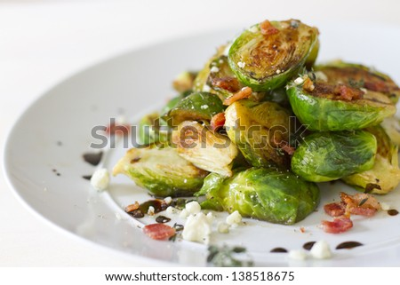 Carmelized brussel sprouts with bacon, blue cheese, thyme, and balsamic reduction. - stock photo