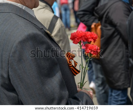 Carnation flowers in a hand of unidentified veteran. Selective focus.
