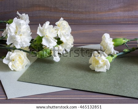 Carnation flowers on wooden flowers with cards for text