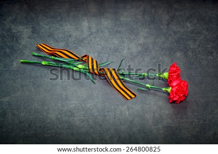 Carnations and St. George ribbon on a dark background. 70 years anniversary of Victory in Great Patriotic War - stock photo
