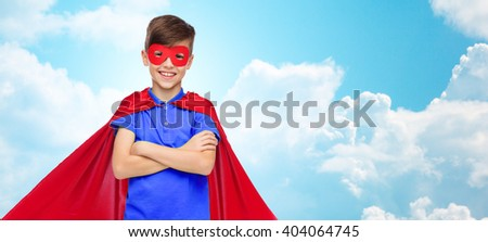 carnival, childhood, power, gesture and people concept - happy boy in red super hero cape and mask over blue sky and clouds background - stock photo