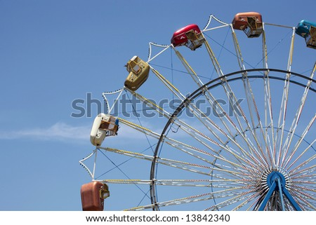 Carnival ferris wheel with blue sky background - stock photo
