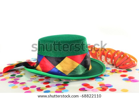 Carnival hat, confetti and streamer on white background