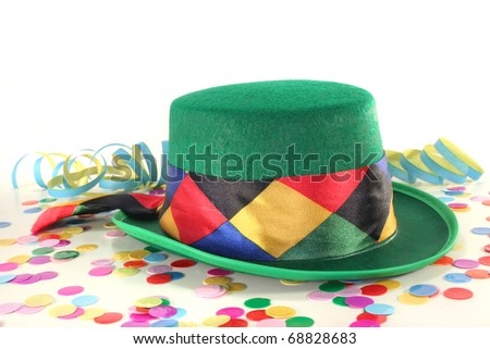 Carnival hat with colorful confetti and streamers on white background - stock photo