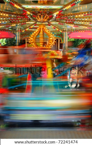 Carnival impressions Merry-go-round with cars at a funfair - stock photo