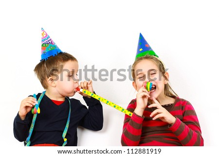 Carnival kids have a fun with noisemaker - stock photo