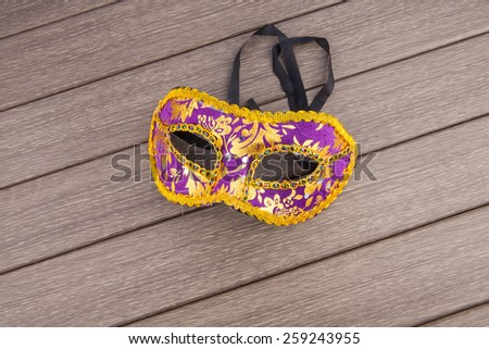 Carnival mask in violet and gold on wooden background - stock photo