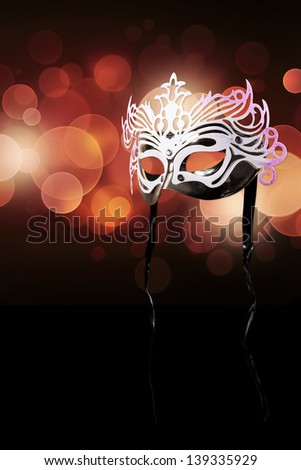 Carnival mask on a black background with red glares - stock photo