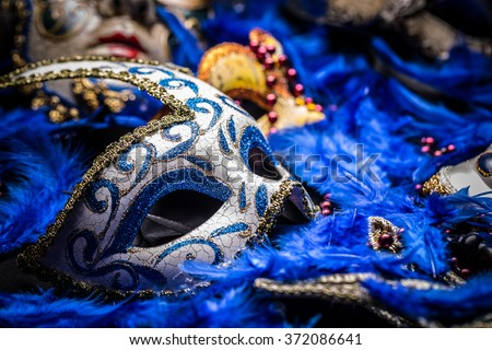Carnival mask on blue feather background