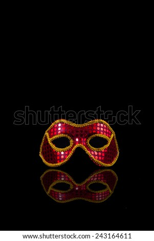 Carnival mask red floating on a black background with reflection effect. - stock photo