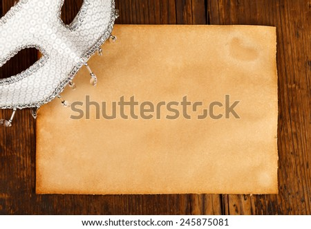 Carnival mask with empty old paper on wooden background - stock photo