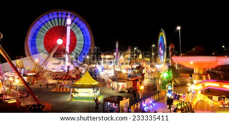 Carnival rides in action at night. - stock photo