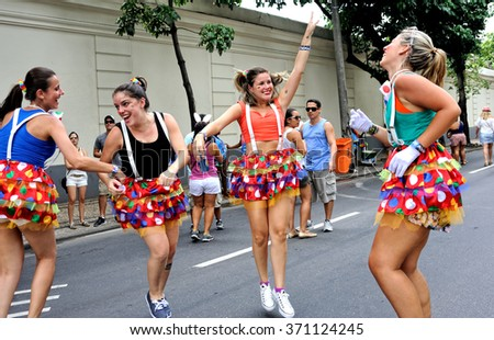 Carnival, Rio de Janeiro, Brazil - February 17, 2015: Colorful costumed participants enjoy the traditional block known as 'Vagalume O Verde'. - stock photo