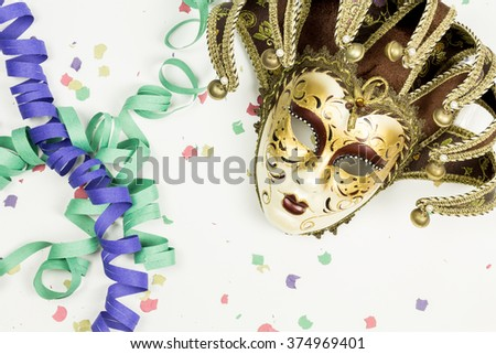 Carnival Venetian mask with confetti and streamers on white background - stock photo