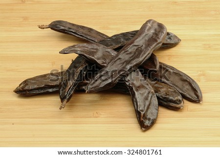 Carobs on wood - stock photo