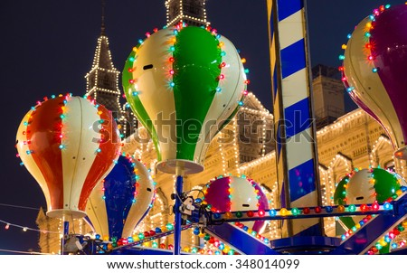 Carousel at Christmas Fair in old town at evening. - stock photo