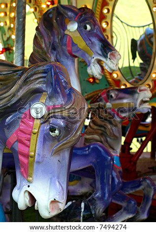 Carousel horses against the bright colors of the merry-go-round - stock photo