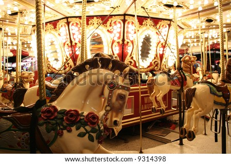 Carousel merry-go-round ride with galloping horses at an amusement park.