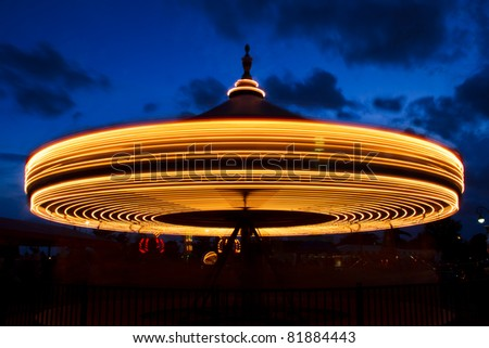 Carousel (merry-go-round) time lapse photo shot in late evening light at a carnival. - stock photo