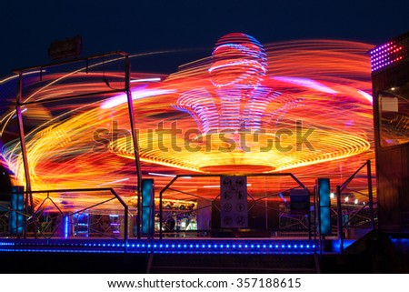 Carousels at night / The visitor amusement park, a very fun and fast carousel for adults.