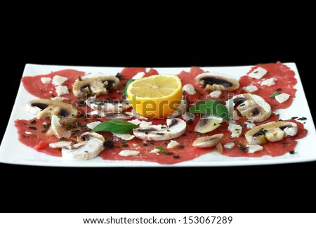 Carpaccio: beef carpaccio served with mushrooms, parmesan, basil, lemon and olive oil. On white plate with black background. - stock photo