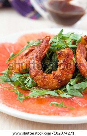 Carpaccio of grapefruit with rucola, arugula salad and spicy fried prawns, shrimp