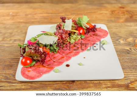 Carpaccio with olives, tomatoes and parmesan, fresh beef - italian cuisine dish