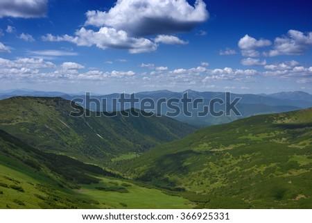 Carpathian mountains view from mountain summer green grass cloudy sky - stock photo