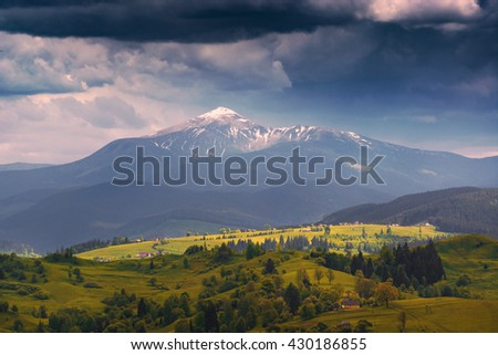 Carpathian valley with highest mountain of Ukraine on a skyline. Spring meadow covered with fresh green grass.