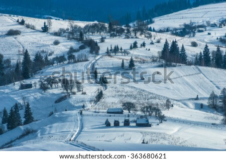 Carpathian village on a mountain hill covered by fresh january snow. Winter landscape. Ukraine, Europe
