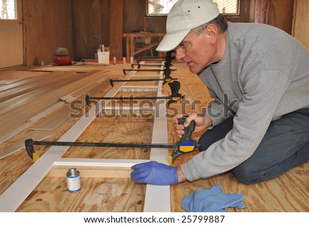 Carpenter adjusting clamp on exterior trim assembly - stock photo