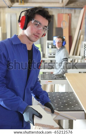 Carpenter and apprentice in workshop - stock photo